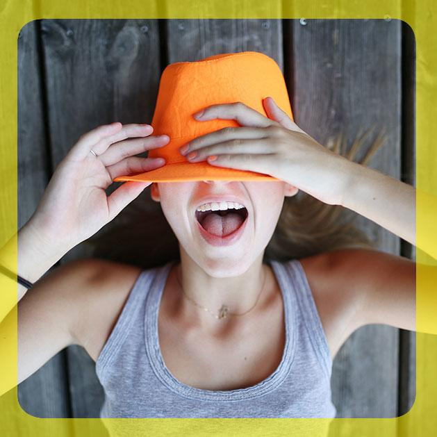 girl covering half of her face with an organe hat