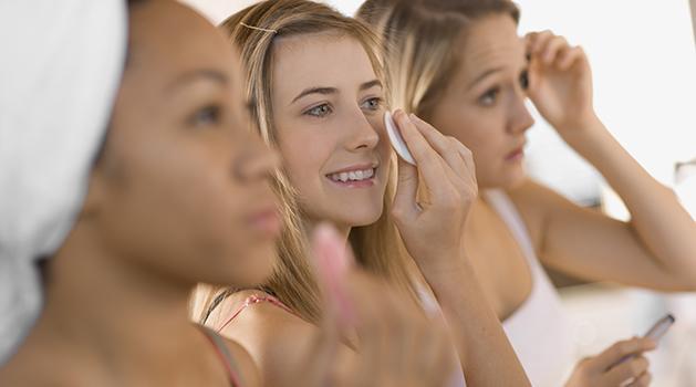 three girls putting on makeup